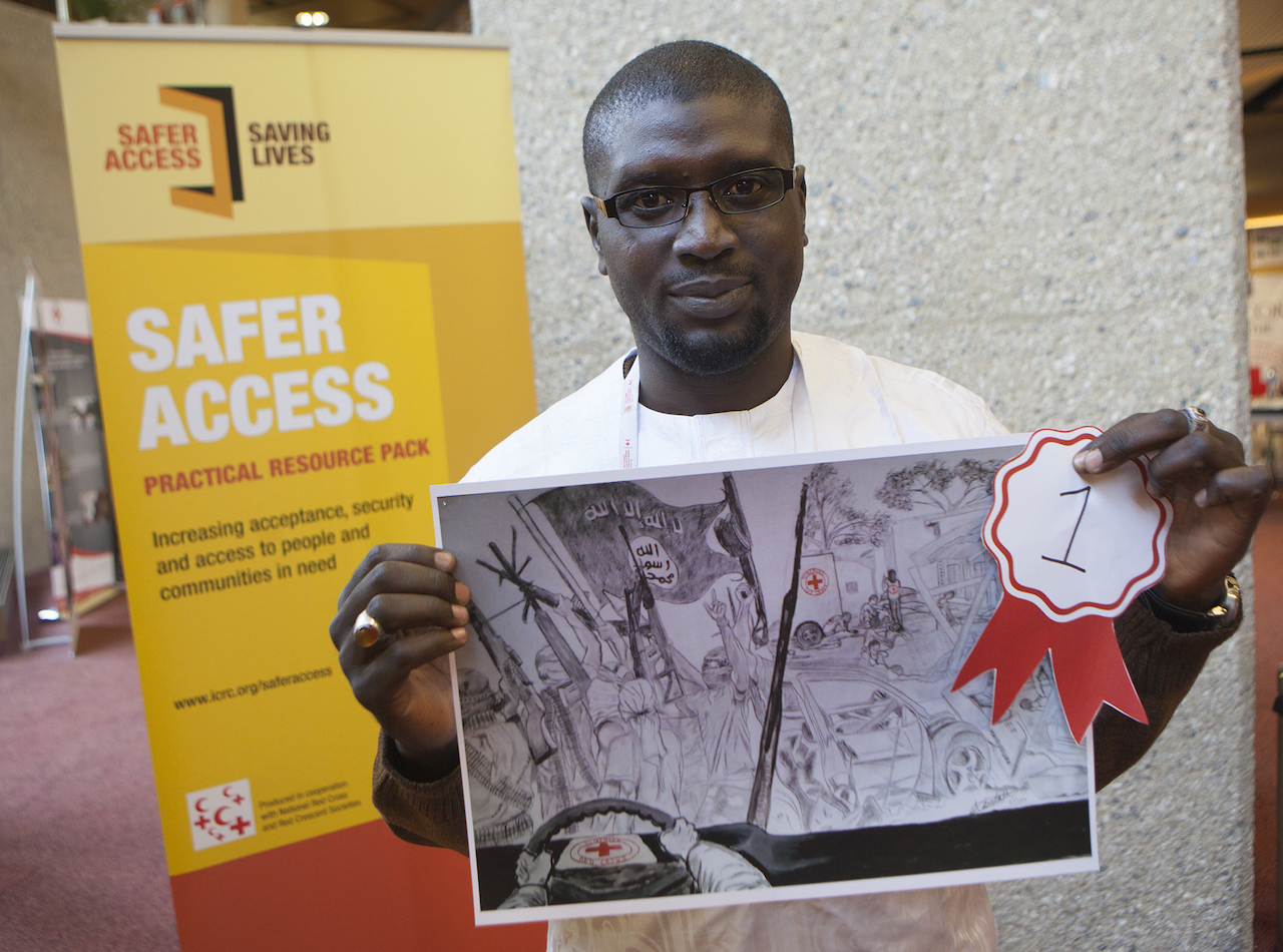 Shamsuddeen Sani Muazu of the Nigerian Red Cross holds the Safer Access award-winning illustration, as the representative for the winning artist, 22-year-old Abraham Adeyemo Adedayo. The award was announced during the 32nd International Conference of the Red Cross and Red Crescent in Geneva, Switzerland, Wednesday, December 9, 2015.