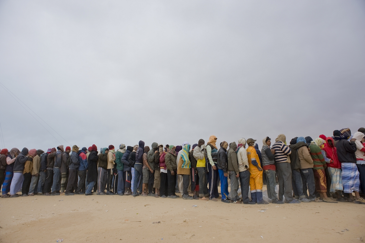 Migrant workers displaced by the conflict in Libya queue for food at the Choucha transit camp in Tunisia