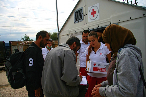 FYR of Macedonia. Tabanovce, 2015. Elena Apostolovska (19) distributing relief to migrants at Tabanovce, the last stop for migrants before entering into Serbia. Red Cross of FYR of Macedonia distributes water, food, hygiene articles and provides medical attention to the tens of thousands of migrants that are moving through the country towards EU.